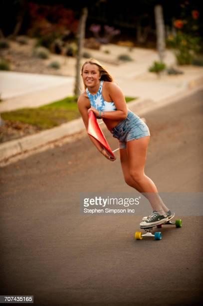 Caucasian girl skateboarding on hill carrying surfboard
