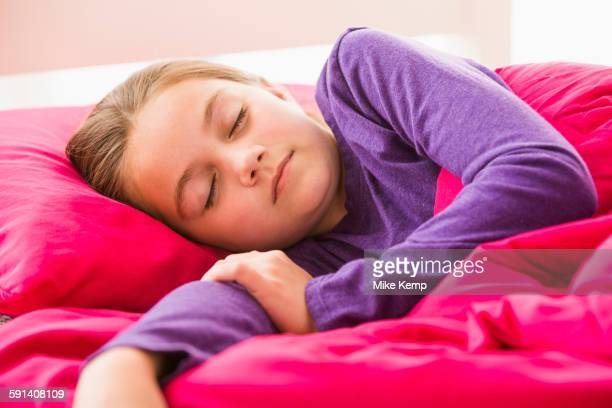 Caucasian girl sleeping in bed