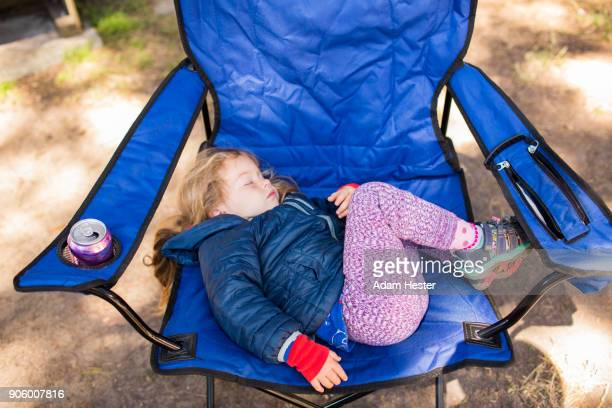 Caucasian girl sleeping on folding chair
