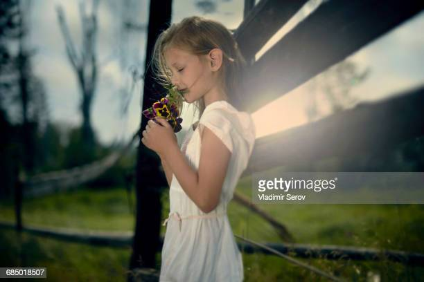 Caucasian girl smelling bouquet of wildflowers near wooden fence