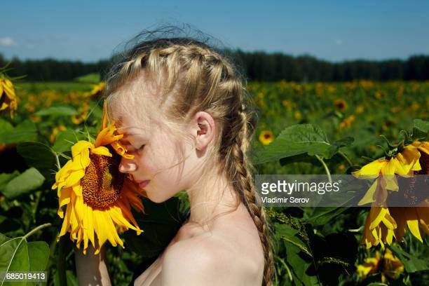Caucasian girl smelling sunflower