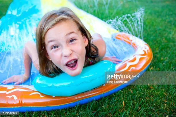 Caucasian girl smiling on water slide