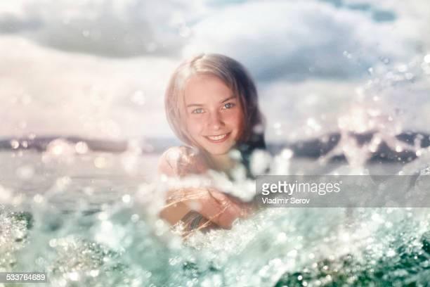 Caucasian girl splashing in lake