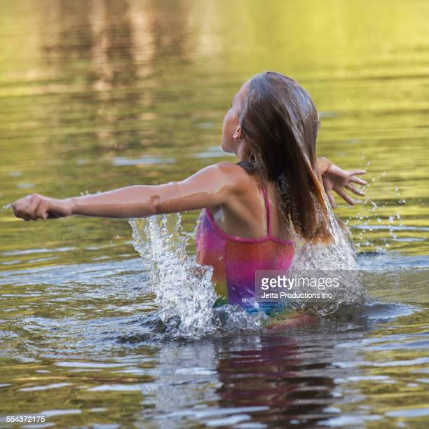Caucasian girl splashing in lake