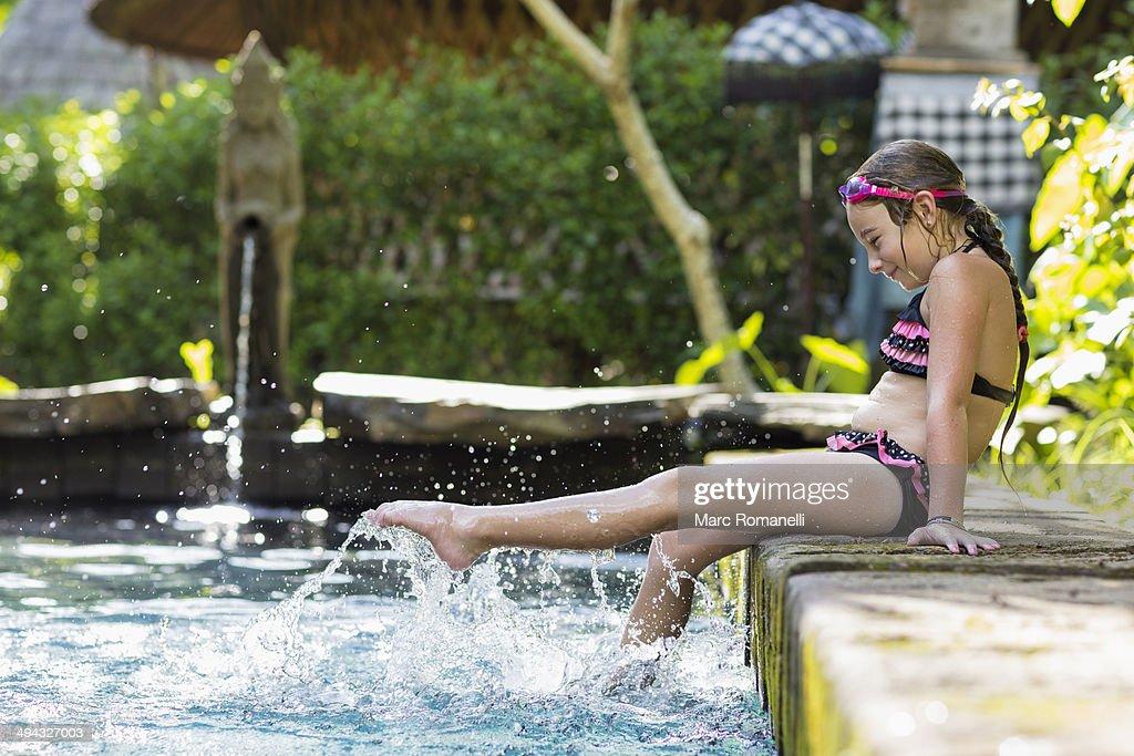 Caucasian girl splashing in swimming pool : Stock Photo
