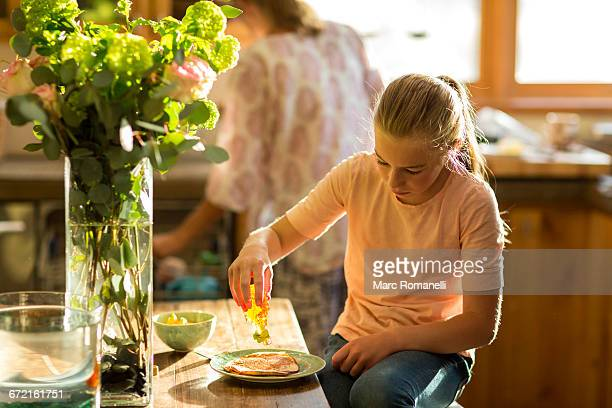 Caucasian girl squeezing honey from bottle onto pancake