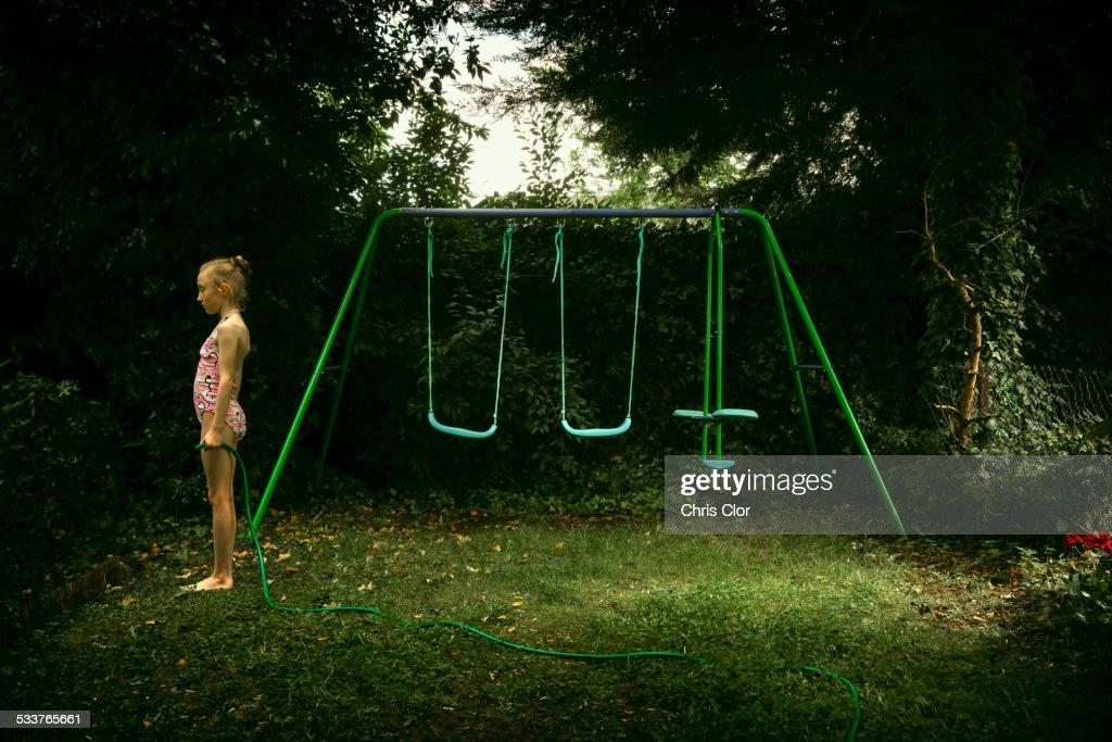 Caucasian girl standing near swing set in backyard : Foto stock