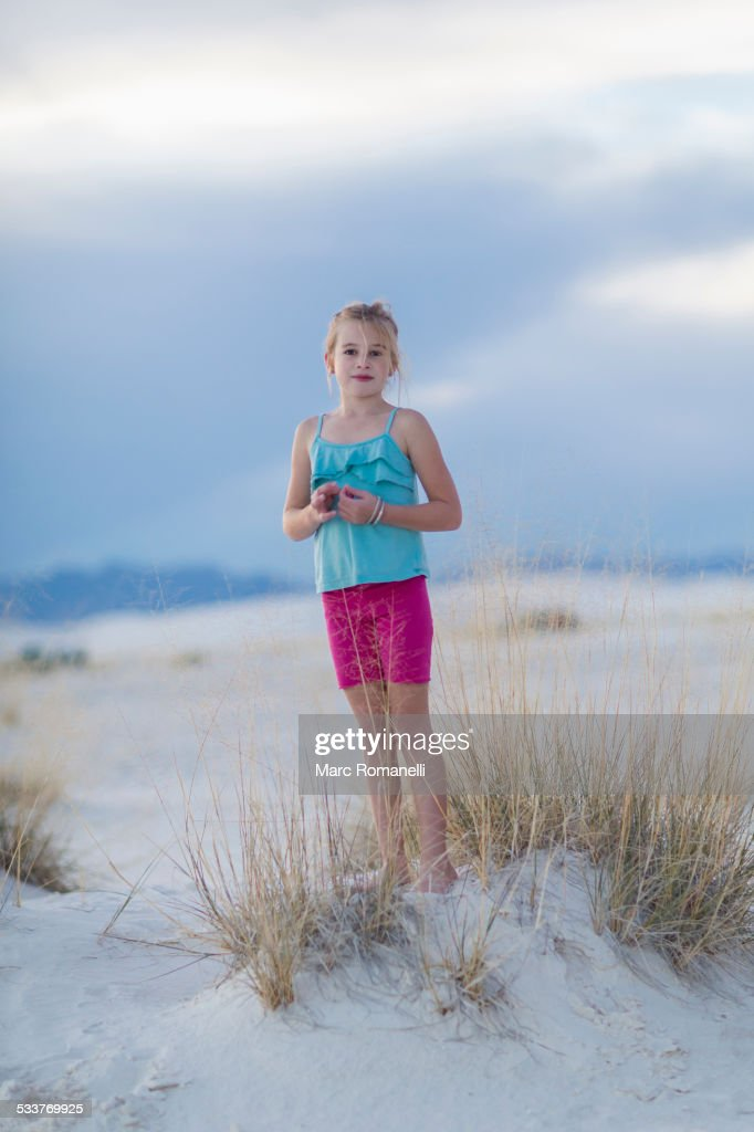 Caucasian girl standing on sand dune : Foto stock