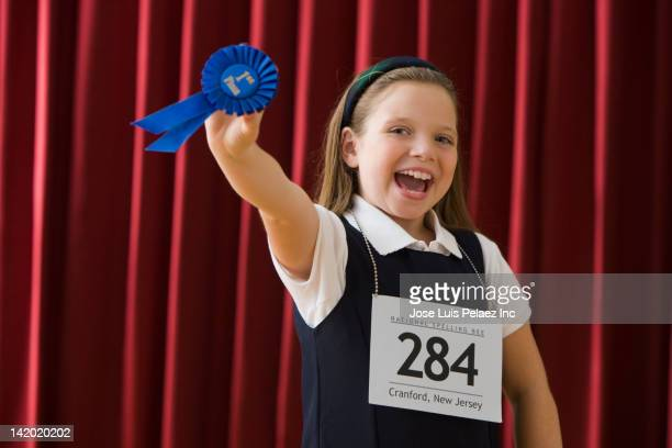 Caucasian girl standing on stage wearing competition number and holding blue ribbon