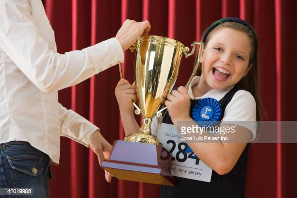caucasian girl standing on stage wearing competition number and receiving trophy - 授賞式 ストックフォトと画像
