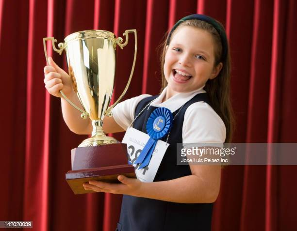 Caucasian girl standing on stage wearing competition number and holding trophy