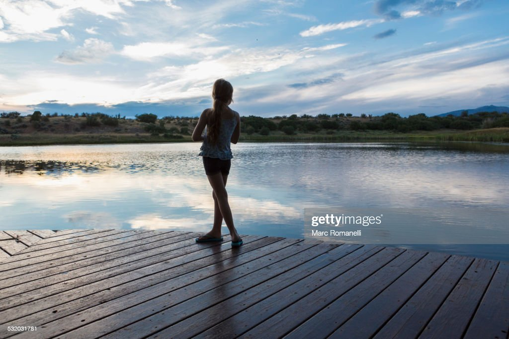 Caucasian Girl Standing On Wooden Deck Near Lake High-Res ...