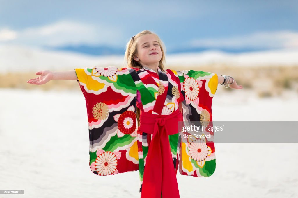Caucasian girl standing with arms outstretched on sand dune : Foto stock