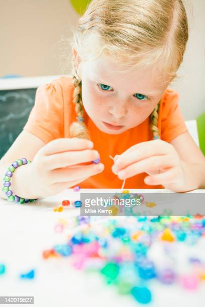 Caucasian girl stringing beads