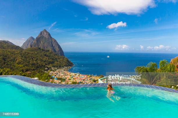 caucasian girl swimming in infinity pool - bottomless girl stock pictures, royalty-free photos & images