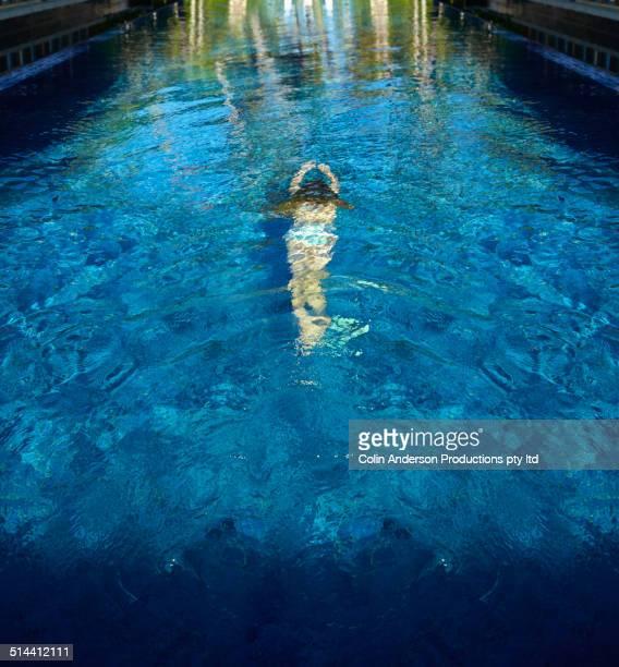 Caucasian girl swimming in pool