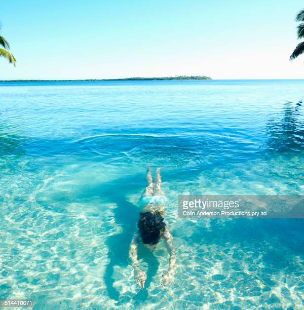Caucasian girl swimming in tropical ocean
