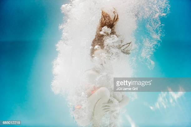 Caucasian girl swimming underwater holding nose