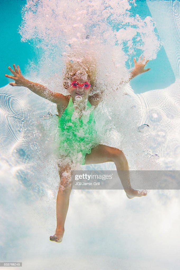 Caucasian girl swimming underwater in pool : Foto stock