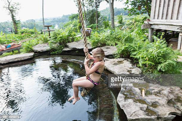 Caucasian girl swinging on rope above pool
