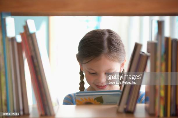 caucasian girl taking book from shelf - spelling stock pictures, royalty-free photos & images