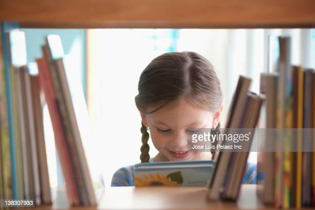 caucasian girl taking book from shelf - 綴り ストックフォトと画像