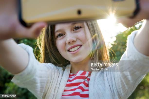 Caucasian girl (9-13) taking selfie