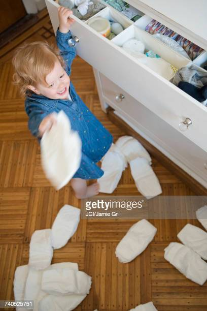 Caucasian girl throwing diapers on floor