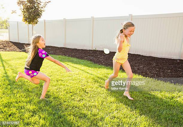 Caucasian girl throwing water balloons in backyard