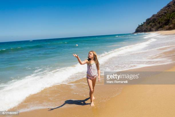 caucasian girl tossing rock at beach - beautiful mexican girls stock photos and pictures