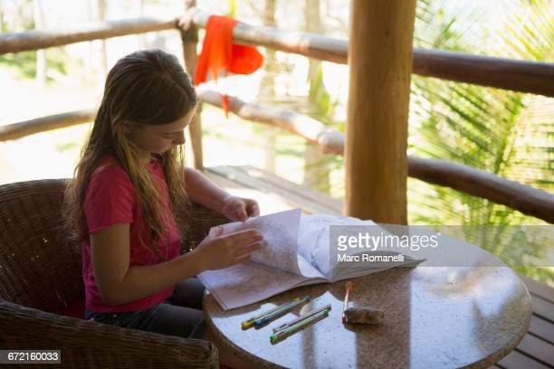 Caucasian girl turning pages of sketchpad on patio