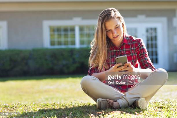 Caucasian girl using cell phone in backyard