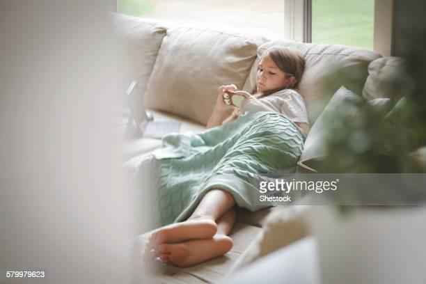 Caucasian girl using cell phone on sofa