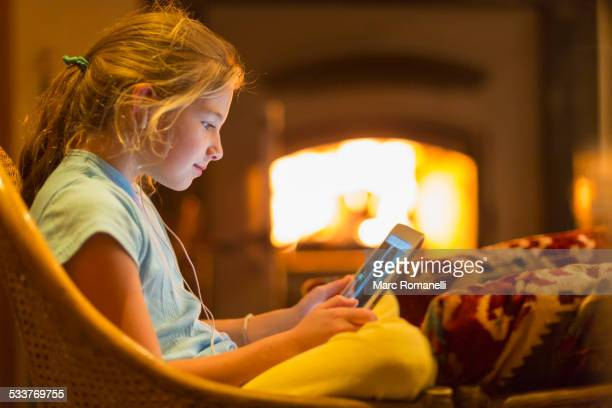 Caucasian girl using digital tablet in living room