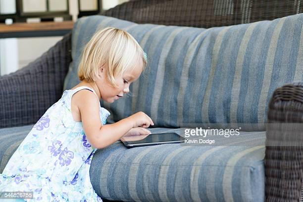 Caucasian girl using digital tablet on sofa