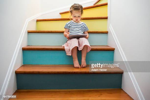 caucasian girl using digital tablet on staircase - niñas fotografías e imágenes de stock