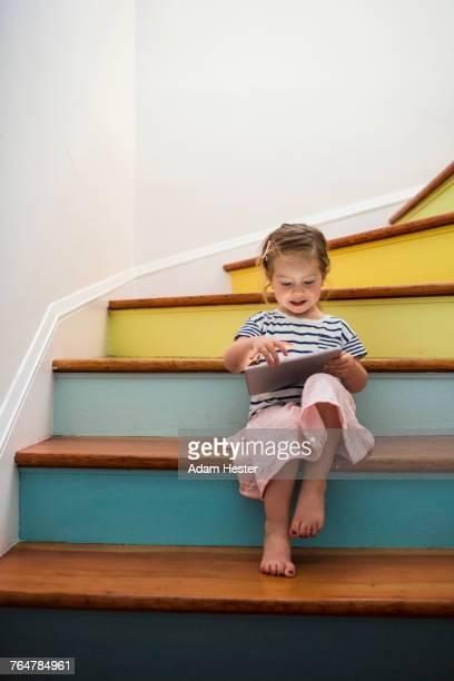 caucasian girl using digital tablet on staircase - nur kinder stock-fotos und bilder