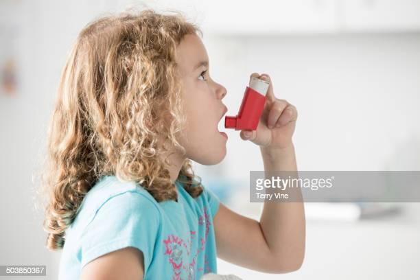 Caucasian girl using inhaler in doctor's office