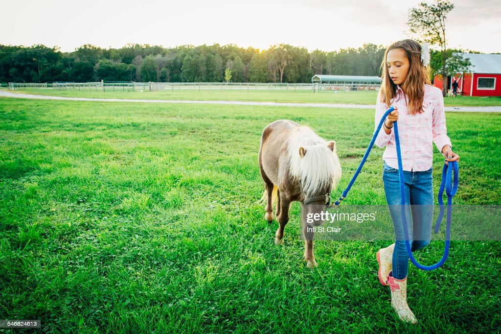 Caucasian girl walking miniature horse on farm