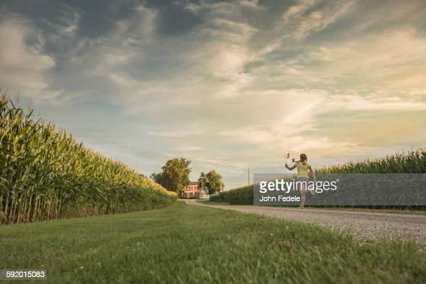 Caucasian girl walking on dirt path by corn field