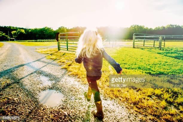 Caucasian girl walking on dirt road on ranch