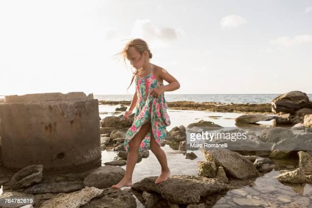 Caucasian girl walking on rocks at beach
