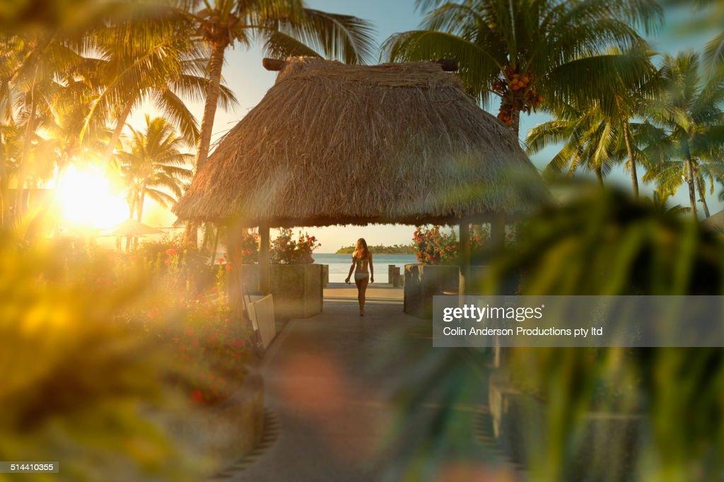 Caucasian girl walking under hut in tropical beach : Stock Photo