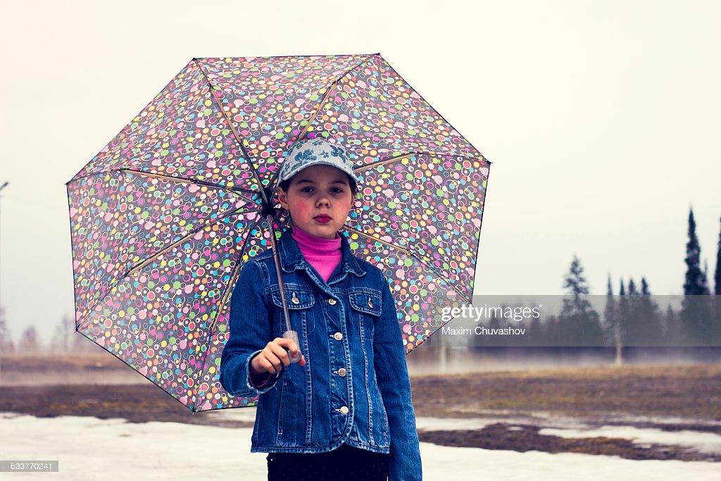 Caucasian girl walking under umbrella in snowy field : Foto stock