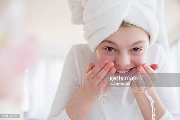 Caucasian girl washing face in bathroom