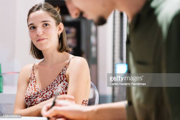 caucasian girl watching her boyfriend while she writes in her notebook - flirting stock pictures, royalty-free photos & images