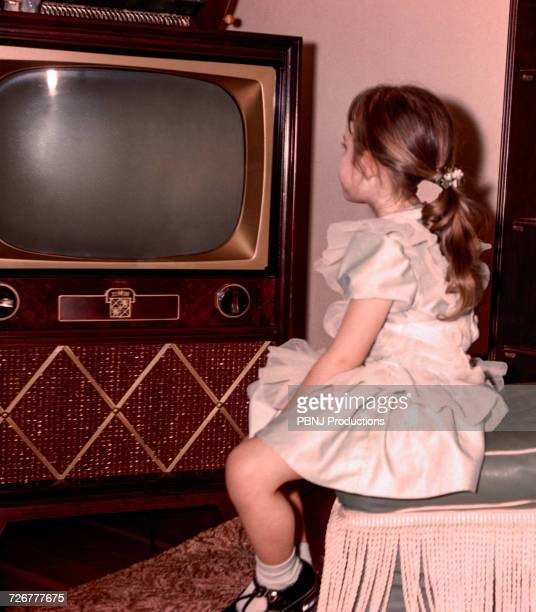 Caucasian girl watching vintage television