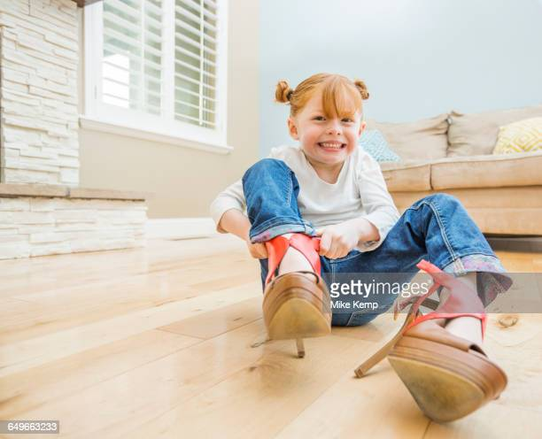 Caucasian girl wearing adult shoes in living room