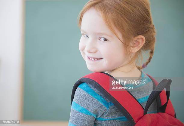 Caucasian girl wearing backpack in classroom