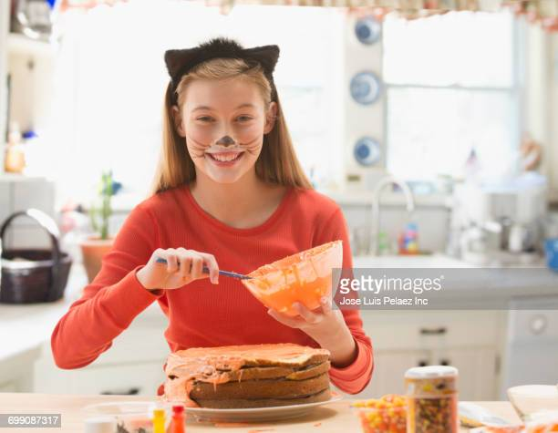 caucasian girl wearing cat costume spreading icing on halloween cake - cat costume stock photos and pictures